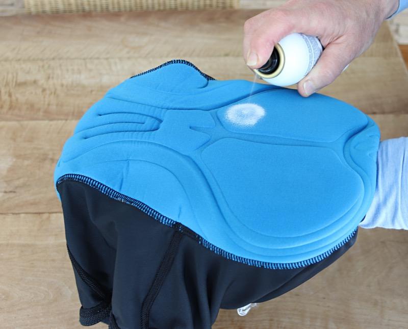 DAs Bild zeigt das Aufsprühen der Tunap Sitzcreme auf ein Hosenpolster